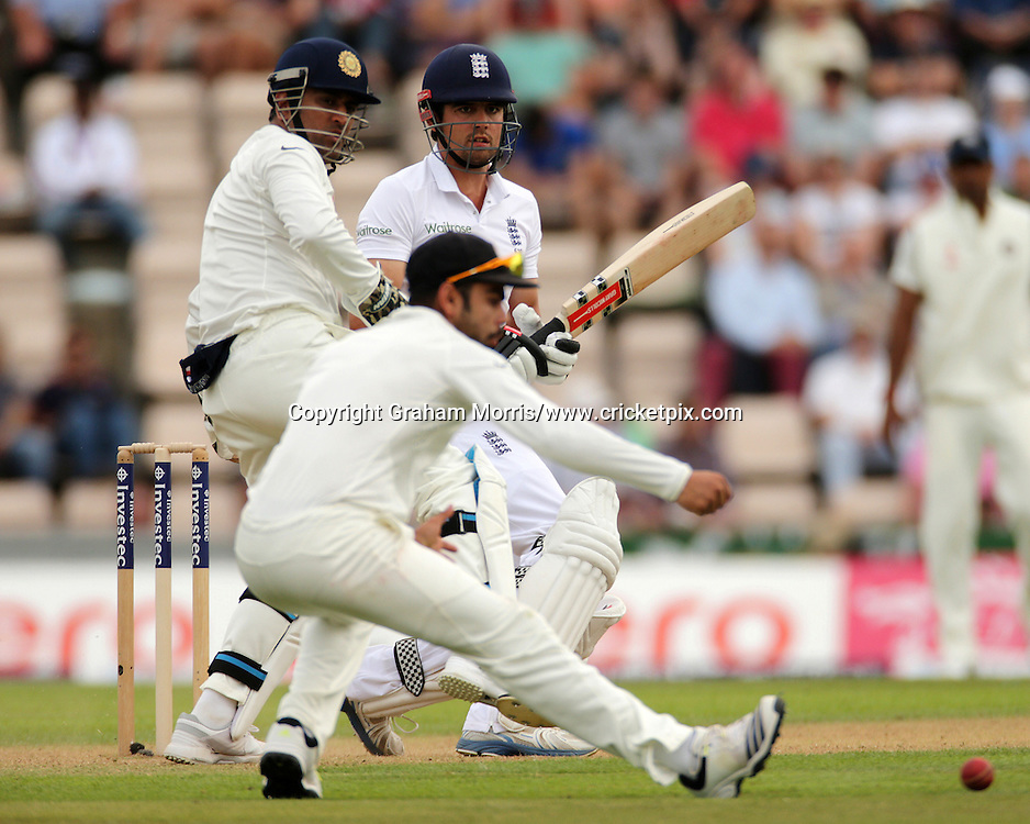 Alastair Cook past wicket keeper Mahendra Singh Dhoni and slip fielder Virat Kohli during the third Investec Test Match between England and India at the Ageas Bowl, Southampton. Photo: Graham Morris/www.cricketpix.com (Tel: +44 (0)20 8969 4192; Email: graham@cricketpix.com) 27/07/14