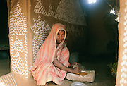 Indian woman grinding spices to prepare meal at her home