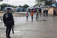 Calais, Pas-de-Calais, France - 17.10.2016    <br />  <br /> A policeman standing with a gas granate  launcher at the &rdquo;Jungle&quot; refugee camp on the outskirts of the French city of Calais. Many thousands of migrants and refugees are waiting in some cases for years in the port city in the hope of being able to cross the English Channel to Britain. French authorities announced that they will shortly evict the camp where currently up to up to 10,000 people live.<br /> <br /> Ein Polizist steht mit einem Gasgranatenwerfer am  &rdquo;Jungle&rdquo; Fluechtlingscamp am Rande der franzoesischen Stadt Calais. Viele tausend Migranten und Fluechtlinge harren teilweise seit Jahren in der Hafenstadt aus in der Hoffnung den Aermelkanal nach Gro&szlig;britannien ueberqueren zu koennen. Die franzoesischen Behoerden kuendigten an, dass sie das Camp, indem derzeit bis zu bis zu 10.000 Menschen leben K&uuml;rze raeumen werden. <br /> <br /> Photo: Bjoern Kietzmann