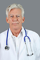 Portrait of confident senior doctor with stethoscope around neck over gray background