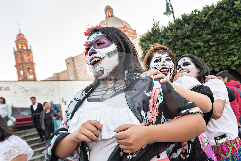 Young women dressed as a La Calavera Catrina dance during the Day of the Dead festival October 27, 2016 in San Miguel de Allende, Guanajuato, Mexico. The week-long celebration is a time when Mexicans welcome the dead back to earth for a visit and celebrate life.
