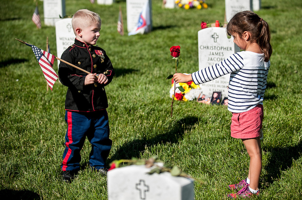 Sophia Namvar, 5, of San Antonio, Texas, offers a rose to Christian Jacobs, 3, of Hertford, North Carolina at Arlington National Cemetery in Arlington, Virginia, USA, on 26 May 2014. Jacobs was visiting the grave of his father, Marine Sgt. Christopher Jacobs, with his mother, Brittany.