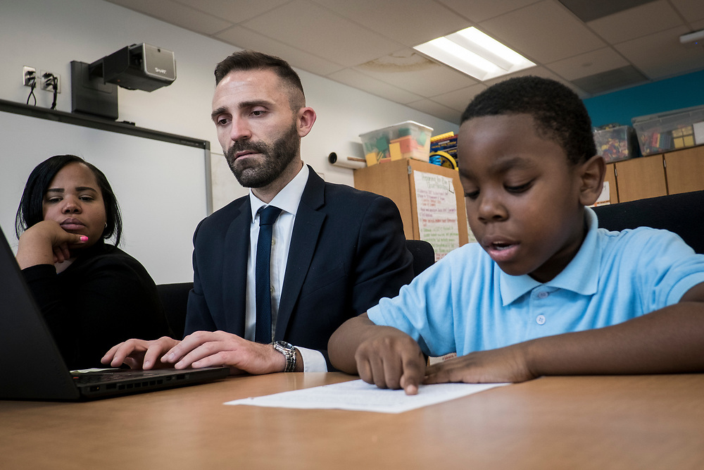 Another teacher looks on as Eric Christopher, Leap ELA Instructional Coach at Turner Elementary School in Washington, D.C., tests a student's reading abilities and comprehension on Wednesday, May 4, 2017.