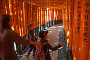 Visitors walk through the succession of orange Toril gates leading to the Fushimi Inari Shrine in Kyoto.