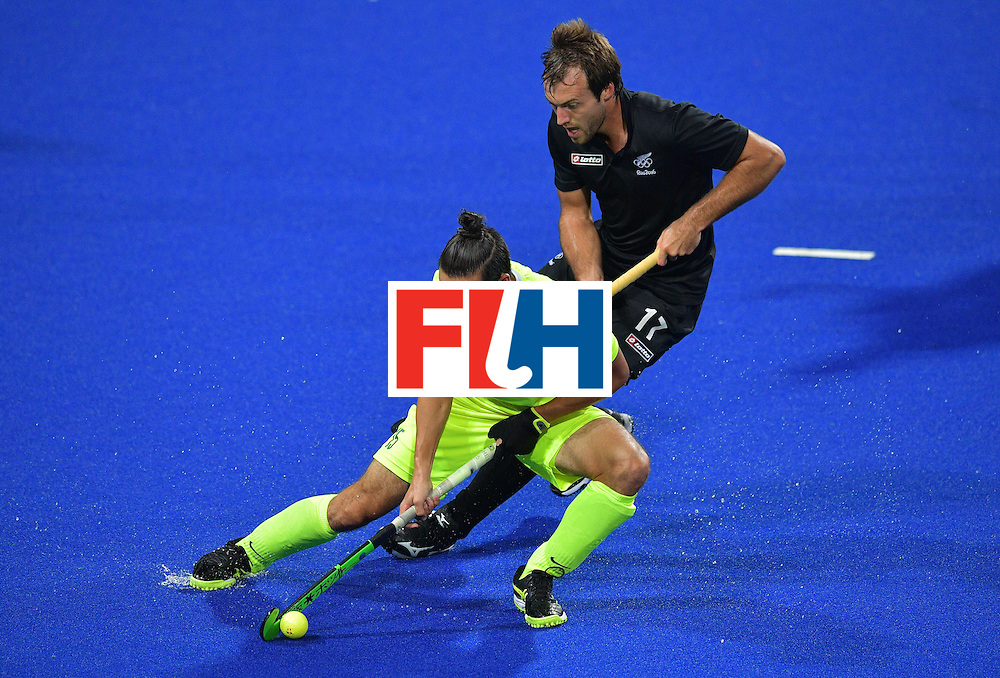 Brazil's Patrick van der Heijden (font) and New Zealand's Nic Woods vie for the ball during the men's field hockey New Zealand vs Brazil match of the Rio 2016 Olympics Games at the Olympic Hockey Centre in Rio de Janeiro on August, 10 2016. / AFP / Carl DE SOUZA        (Photo credit should read CARL DE SOUZA/AFP/Getty Images)