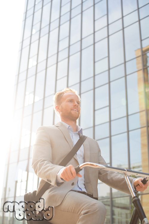 Low angle view of businessman riding bicycle outside office building on sunny day