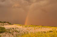 A sunset rainbow paints an arc of color over the dunes at Head of the Meadow Beach.