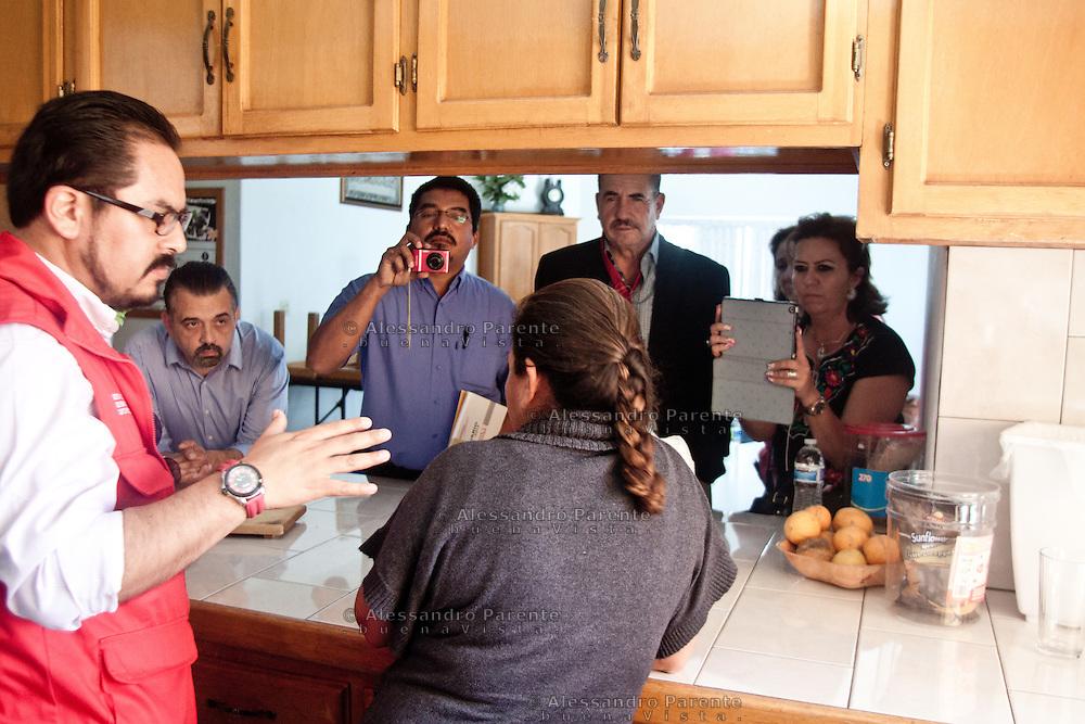 Un gruppo di politici della regione di Guerrero visitano la casa delle migranti. La donna di spalle ha paura che questi, in collusione con la mafia che la cerca, siano venuti ad identificarla.