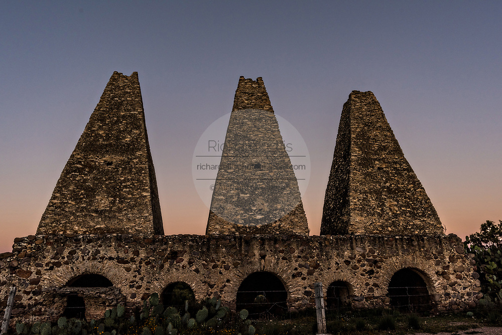 Sunset over the cone shaped smelting towers of the shuttered mine of the Santa Brigida Hacienda in the ghost town of Mineral de Pozos, Guanajuato, Mexico. The town, once a major silver mining center was abandoned and left to ruin but has slowly comeback to life as a bohemian arts community.