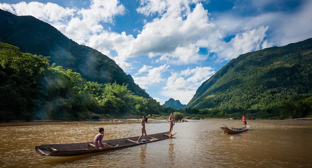 Boys on boats on Nan Ou river at Muang Ngoi (Laos)