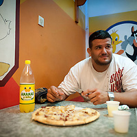 02/07/2012. Senegal, Dakar. One day with the White Lion.    The canarian wrestler Juan Espino, the unique white fighter in the senegalese wrestling. Ready to eat his pizza .  ©Sylvain Cherkaoui