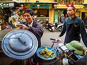 "21 DECEMBER 2017 - HANOI, VIETNAM: A vendor sells Vietnamese hot drinks from his bicycle in the old quarter of Hanoi. The old quarter is the heart of Hanoi, with narrow streets and lots of small shops but it's being ""gentrified"" because of tourism and some of the shops are being turned into hotels and cafes for tourists and wealthy Vietnamese.   PHOTO BY JACK KURTZ"