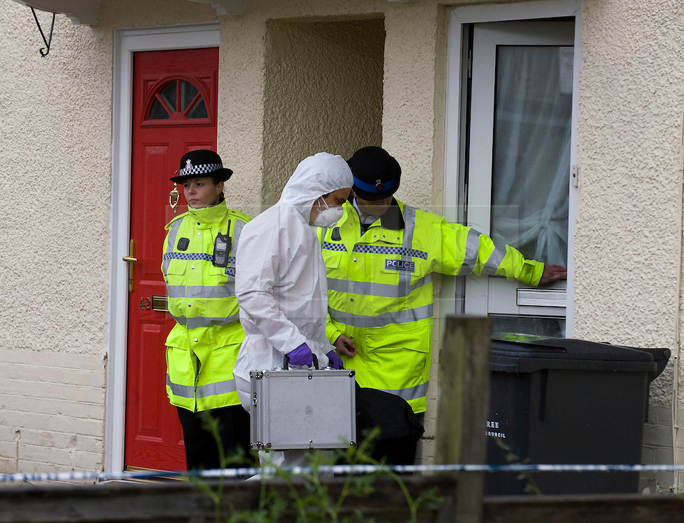 © licensed to London News Pictures. Braintree, UK  06/06/2011. Forensics entering a property (white door) on Bartram Avenue in Braintree, Essex today (06/06/2011) where the bodies of a woman and a child were found following a shooting. Officers were called to reports of a firearms incident in the early hours of the morning. Photo credit should read Ben Cawthra/LNP