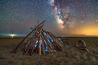 A mysterious wooden stucture is illuminated from within under a bright night sky full of stars at Popham Beach. You can see the Seguin Island Lighthouse casting its light offshore.