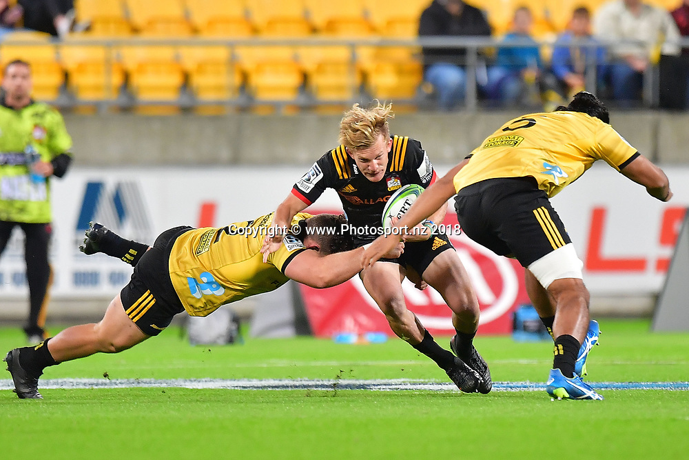 Chiefs' Damian McKenzie (C is tackled by Hurricanes Ricky Riccitelli (L) and Michael Fatialofa during the Hurricanes vs Chiefs Super Rugby match at the Westpac Stadium in Wellington on Friday the 13th of March 2018. Copyright Photo by Marty Melville / www.Photosport.nz
