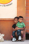 A girl holds a younger boy on her lap in the town of San Esteban, Honduras on Wednesday April 24, 2013.