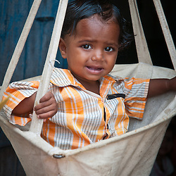 A young child is weighted to check to see if he is getting a proper diet and is not suffering from malnutrition.
