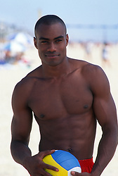 Handsome young shirtless african american man holding a volleyball at the beach