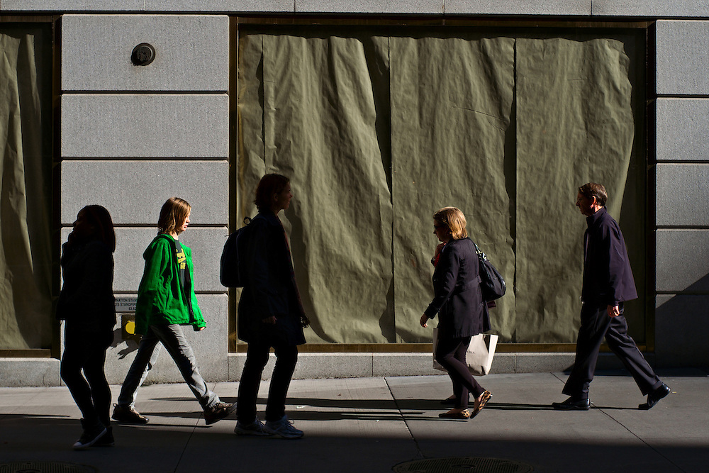 People walking past papered-over shop windows, Wall Street