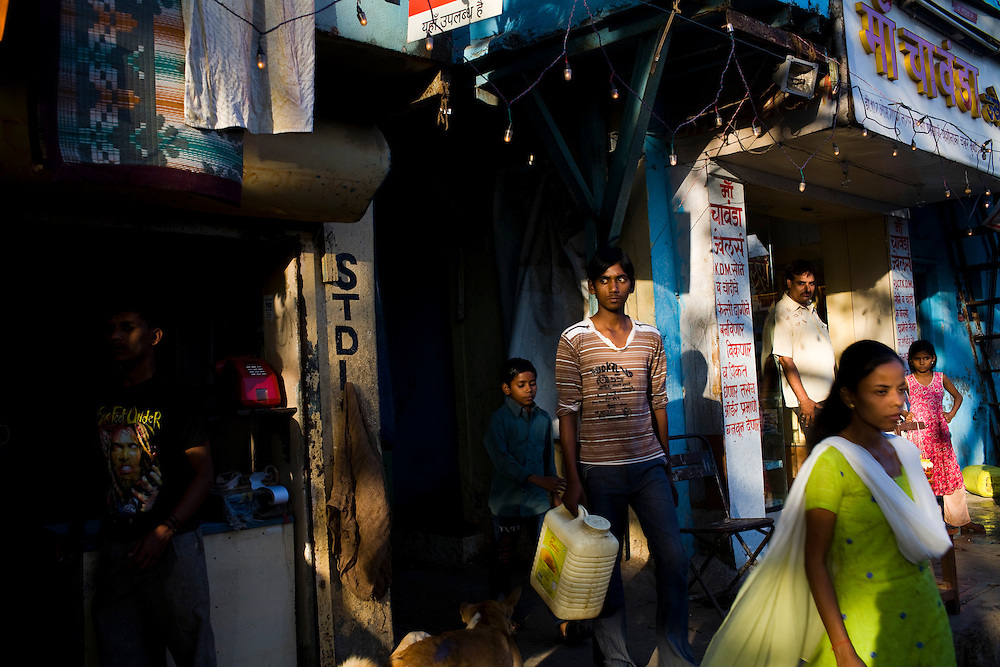 People walk through the Rafik Nagar slum, one of the areas in which Lok Seva Sangam, a local NGO, has set up free TB health clinics.  People in the slums are often too poor to pay for proper health care, let alone the transportation to get them to the hospitals or clinics.