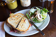 Giant deli bread sandwich with mustard and salad in bar diner restaurant in Soho, New York, USA