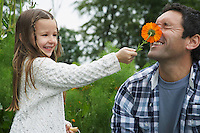 Girl (5-6) sticking flower in father's face outdoors