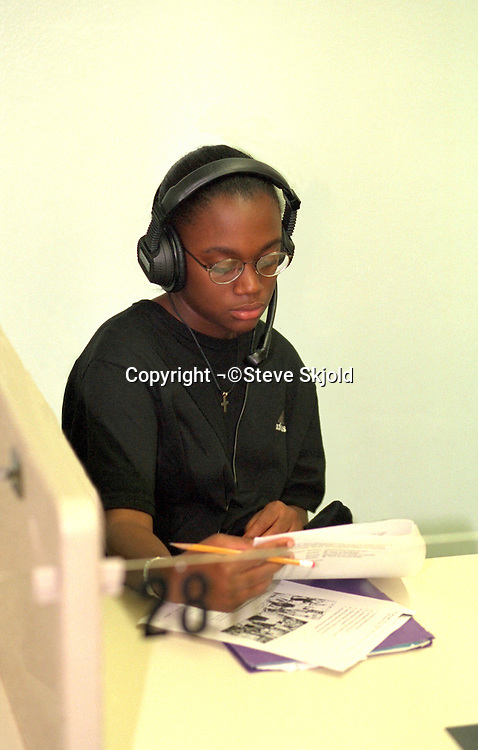 Student age 14 in school language lab with earphones.   New Hope Minnesota USA