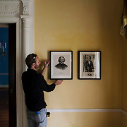 """October 13, 2015 - New York, NY : A curated reinstallation of art and antiques is currently underway in the Mayor's House, Gracie Mansion, as it is being prepped for reopening. Here, Jonathan Elliott, the consulting registrar for the Gracie Mansion Conservancy, hangs """"Frederick Douglass (1818 - 1895), ca. 1873,"""" in the Peach room on Tuesday morning. At right is """"Henry Bibb (1815-1854)"""". Both works are from the Museum of the City of New York. CREDIT: Karsten Moran for The New York TImes"""
