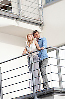 Full length of young couple looking away while standing at hotel balcony