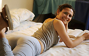 A woman laying on a bed reading a book, UK 2005