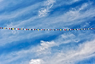 Prayer flags draped across the blue sky over Tiger's Nest monastery in Paro Valley, Bhutan, Asia