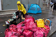 A mother rushes past piled waste in plastic bags awaiting collection by Westminster collection staff in front of a homeless tent on St. Martin's Lane, on 15th June 2019, in London, England.