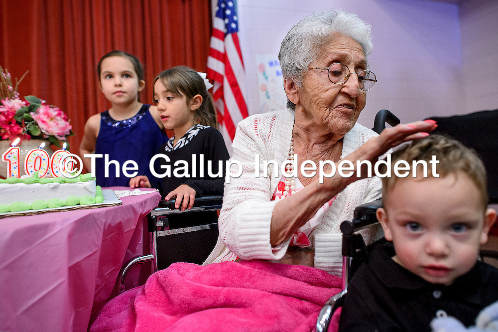 020114       Cable Hoover<br /> <br /> Alice Castillo, center, pats the head of her great, great, great grandson Mateo Savaadra as her great, great grandnieces Lauren Stanage, left, and Sari Omanson get ready to help blow out the candles during Castillo's 100th birthday party at Little Sisters of the Poor in Gallup Saturday.
