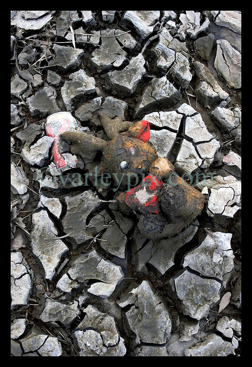 1st Oct, 2005. Hurricane Katrina aftermath, New Orleans, Louisiana. Lower 9th ward. The remnants of the lives of ordinary folks, now covered in mud as the flood waters recede. A teddy bear holding a heart with the word 'Love' written in the middle of a heart lies in the dirt.