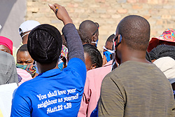 JOHANNESBURG, SOUTH AFRICA - MAY 08: Volunteers and food distribution official instruct people to social distance outside a food distribution centre in Diepsloot on May 08, 2020 in Diepsloot, South Africa. In partnership with with government and Celebration Church, Engen Fuel Retailers contributed food parcels for over 4000 familes in Diepsloot during lockdown level 4. (Photo by Dino Lloyd)