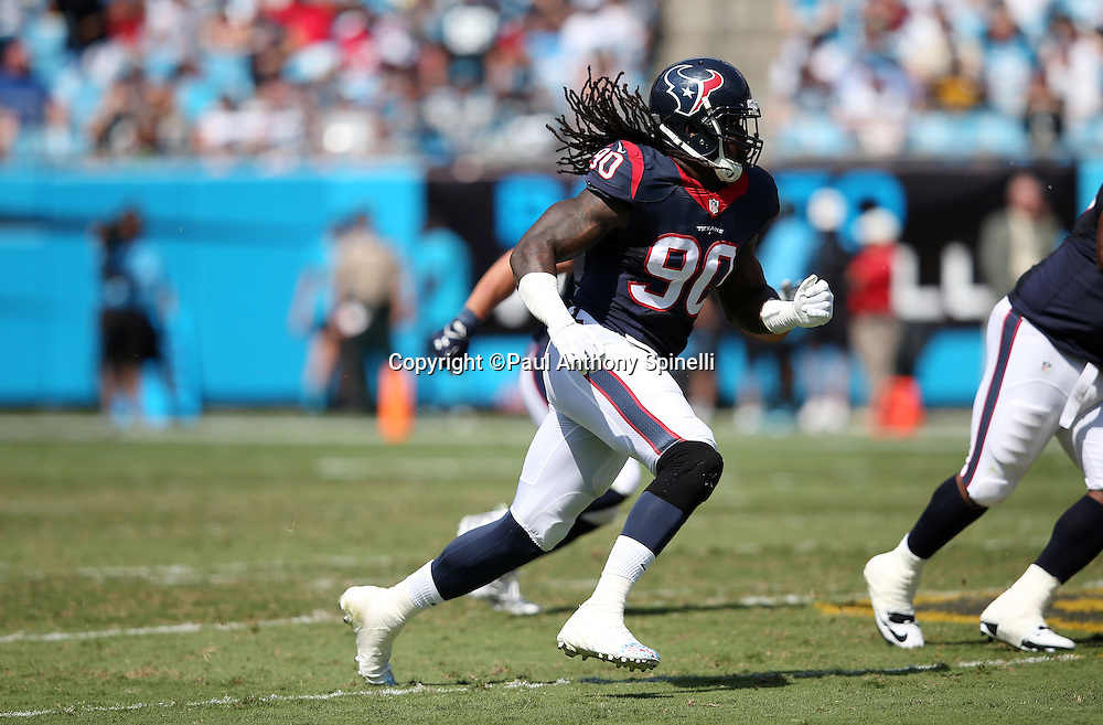 Hair and hair extensions fly behind him as Houston Texans outside linebacker Jadeveon Clowney (90) rushes the quarterback during the 2015 NFL week 2 regular season football game against the Carolina Panthers on Sunday, Sept. 20, 2015 in Charlotte, N.C. The Panthers won the game 24-17. (©Paul Anthony Spinelli)