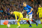 Manu Trigueros (#14) of Villarreal CF is fouled by Scott Arfield (#37) of Rangers FC during the Europa League group stage match between Rangers FC and Villareal CF at Ibrox, Glasgow, Scotland on 29 November 2018.