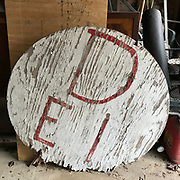 DEI Round Sign from front porch of Margarte's Grocery- red lettering on white background appx 39 in diameter. Was by front railing.<br />