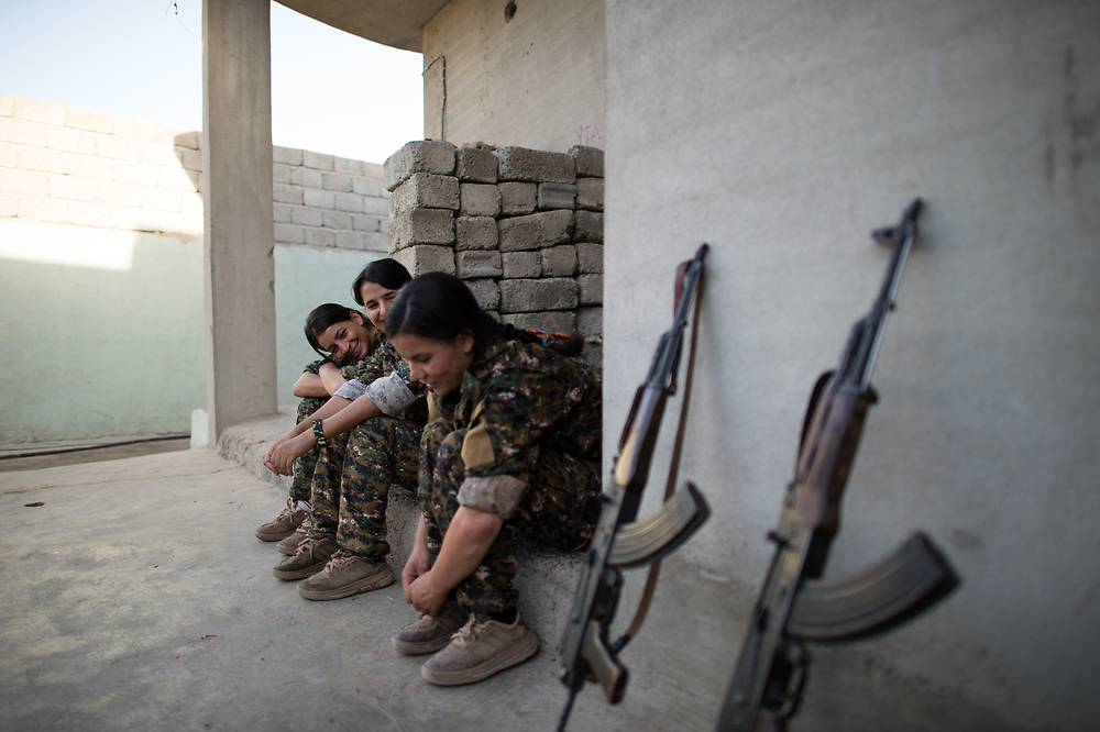 Members of YPJ-Şingal waiting  in front of a house in Shingal to go to the nearby frontline with ISIS. Shingal (Sinjar), Iraq, August 26, 2015