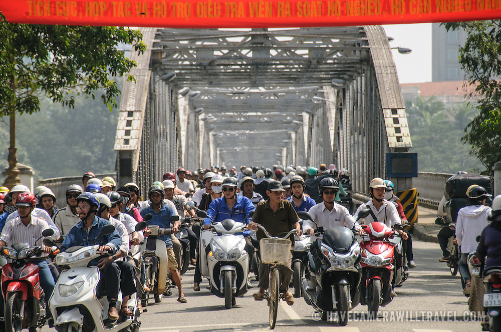 Hundreds of scooters and bikes crossing Cau Truong Tien in afternoon traffic in Hue, Vietnam.