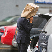 Sean Thompson of Roslyn uses a paper bag to shield himself from the rain outside the Panera Bread off the Sunrise Highway North Service Road in Patchogue Thursday, Sept. 10, 2015.