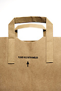 brown paper shopping bag with the text please hold both handles