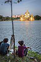 Locals enjoy drinks late afternoon in the grounds of Kandawgyi Lake looking across to Karaweik Hall, Yangon.