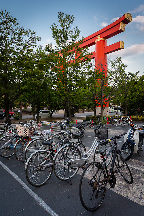 Bikes are parked near the Kyoto library with a huge red Tori in the background.