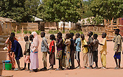 Children waiting in line to wash their hands prior to lunch at the Tangory Transgambienne 2 primary school in the town of Bignona, Senegal on Wednesday June 13, 2007.