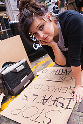 London, July 5th 2014. A woman creates a placard as hundreds protest near the Israeli embassy in London against the ongoing occupation and the west's support of Israel's collective punishment of Palestinians