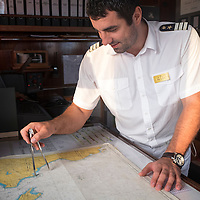 The first officer of the Sea Cloud sailing yacht in the ship's bridge uses nautical tools on charts of Greece while sailing the Mediterranean.