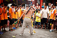 This man is performing a Ji Tong ritual.  The spirit-medium, said to be possessed by the spirit of a Taoist God, self-flagellates at a religious ceremony in Tainan, Taiwan.