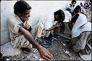 "Drug addicts smoke their daily heroin dose, probably the last of the afternon. Morgh Mandi, one of the most crowded place by the druggies in Rawalpindi. Pakistan, on thursday, August 14 2008.....""Pakistan is one of the countries hardest hits by the narcotics abuse into the world, during the last years it is facing a dramatic crisis as it regards the heroin consumption. The Unodc (United Nations Office on Drugs and Crime) has reported a conspicuous decline in heroin production in Southeast Asia, while damage to a big expansion in Southwest Asia. Pakistan falls under the Golden Crescent, which is one of the two major illicit opium producing centres in Asia, situated in the mountain area at the borderline between Iran, Afghanistan and Pakistan itself. .During the last 20 years drug trafficking is flourishing in the Country. It is the key transit point for Afghan drugs, including heroin, opium, morphine, and hashish, bound for Western countries, the Arab states of the Persian Gulf and Africa..Hashish and heroin seem to be the preferred drugs prevalence among males in the age bracket of 15-45 years, women comprise only 3%. More then 5% of whole country's population (constituted by around 170 milion individuals),  are regular heroin users, this abuse is conspicuous as more of an urban phenomenon. The substance is usually smoked or the smoke is inhaled, while small number of injection cases have begun to emerge in some few areas..Statistics say, drug addicts have six years of education. Heroin has been identified as the drug predominantly responsible for creating unrest in the society."""
