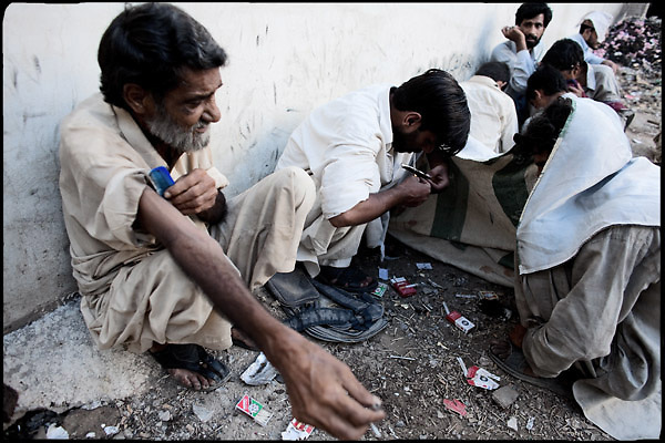 """Drug addicts smoke their daily heroin dose, probably the last of the afternon. Morgh Mandi, one of the most crowded place by the druggies in Rawalpindi. Pakistan, on thursday, August 14 2008.....""""Pakistan is one of the countries hardest hits by the narcotics abuse into the world, during the last years it is facing a dramatic crisis as it regards the heroin consumption. The Unodc (United Nations Office on Drugs and Crime) has reported a conspicuous decline in heroin production in Southeast Asia, while damage to a big expansion in Southwest Asia. Pakistan falls under the Golden Crescent, which is one of the two major illicit opium producing centres in Asia, situated in the mountain area at the borderline between Iran, Afghanistan and Pakistan itself. .During the last 20 years drug trafficking is flourishing in the Country. It is the key transit point for Afghan drugs, including heroin, opium, morphine, and hashish, bound for Western countries, the Arab states of the Persian Gulf and Africa..Hashish and heroin seem to be the preferred drugs prevalence among males in the age bracket of 15-45 years, women comprise only 3%. More then 5% of whole country's population (constituted by around 170 milion individuals),  are regular heroin users, this abuse is conspicuous as more of an urban phenomenon. The substance is usually smoked or the smoke is inhaled, while small number of injection cases have begun to emerge in some few areas..Statistics say, drug addicts have six years of education. Heroin has been identified as the drug predominantly responsible for creating unrest in the society."""""""